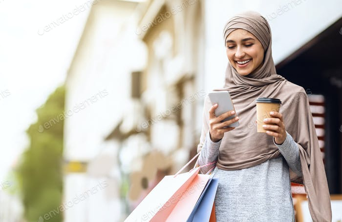 Cheerful arab girl in hijab with shopping bags using phone