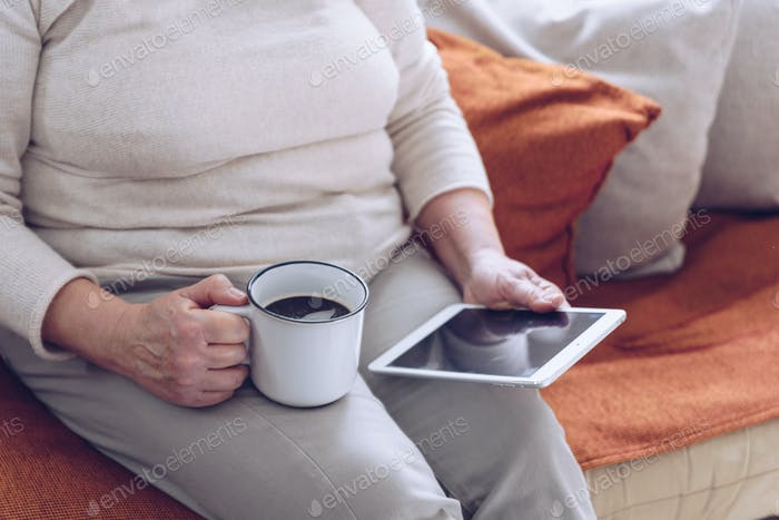 Senior woman with a cup of coffee and tablet  on the sofa