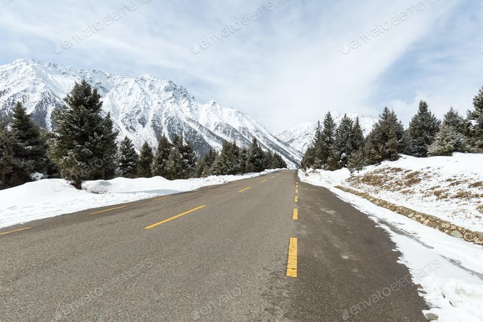 empty asphalt road between the snow mountain