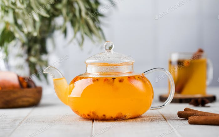 Autumn sea buckthorn tea in a teapot on a white wooden background. Autumn mood.