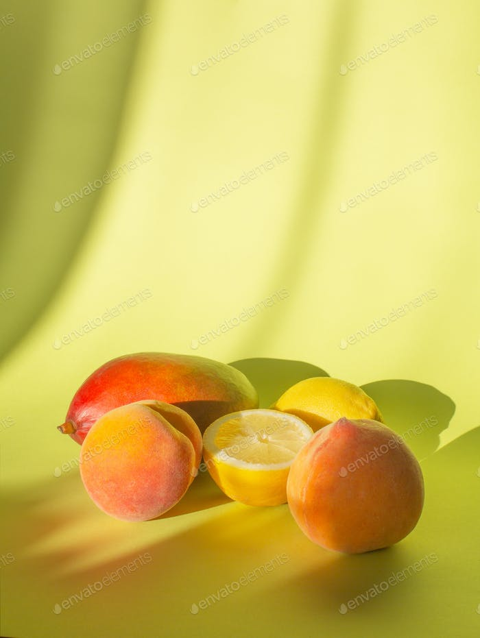 Fresh peaches, lemon and mango on a pastel background with shadows