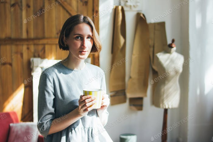 Young woman in simple grey dress with yellow cup sitting on chair in art work studio