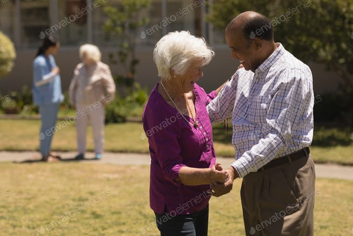 Side view of happy senior couple dancing together in garden on sunny day