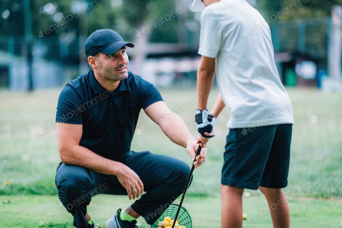 Personal Golf Lesson for Children. Instructor Teaching Young Boy How to Play Golf.