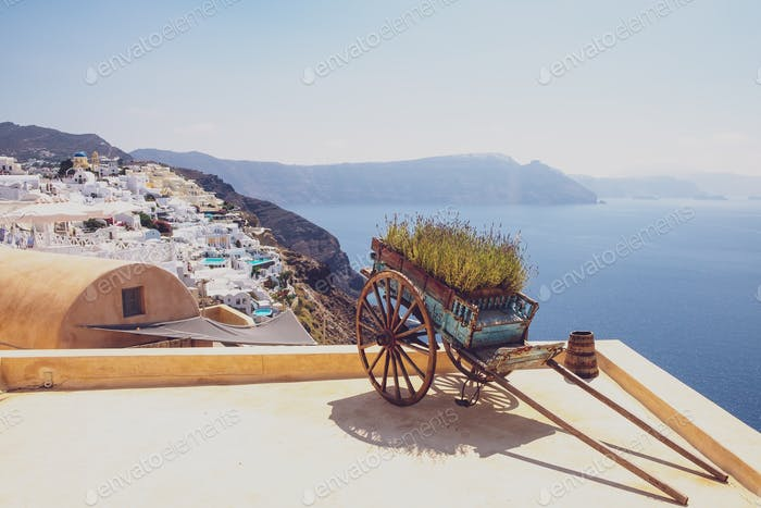 Nice vintage wooden cart with ocean coastline and village background