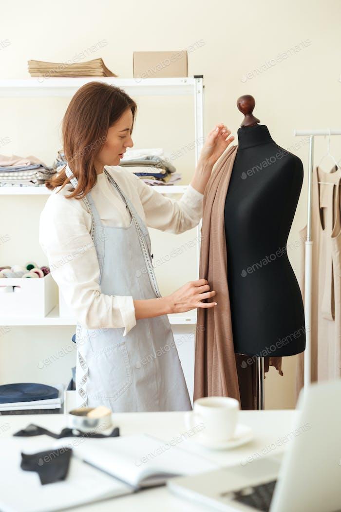 Woman measuring fabric on black dummy