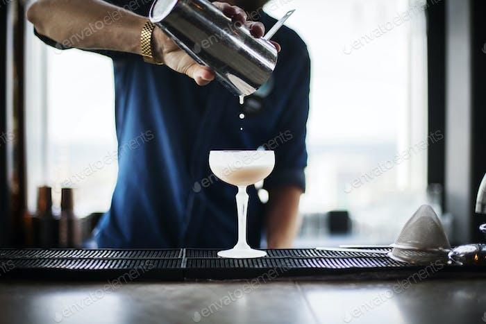 Mittelteil des Barkeepers Gießen Cocktail aus Shaker im Restaurant