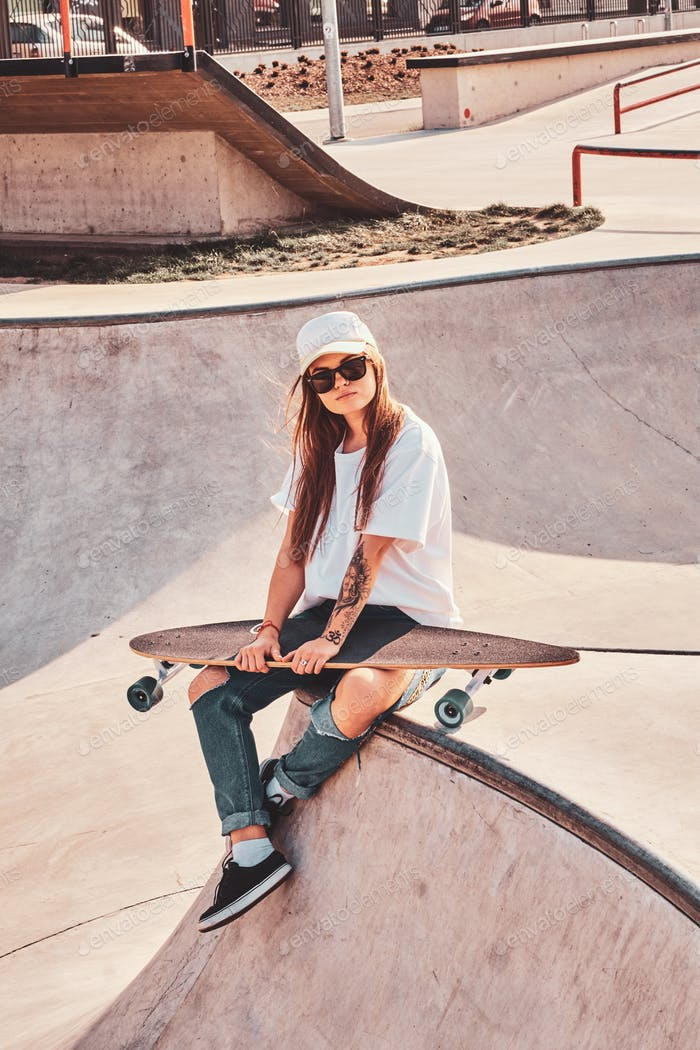 Beautiful young woman in sunglacces and cap is sitting at skatepark