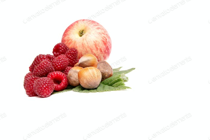 Hazelnuts,apple and raspberries on a white.