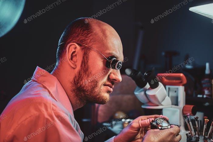 Serious Uhrmacher repariert Cutomers Auftrag in seinem eigenen Reparaturstudio