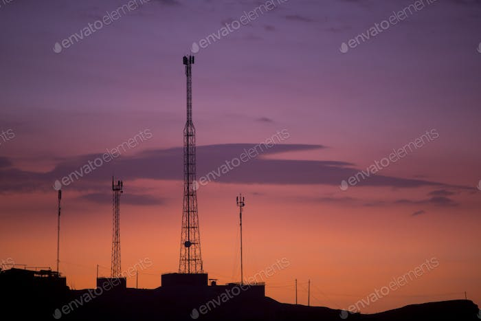 Communication towers on orange purple sky background, Peru