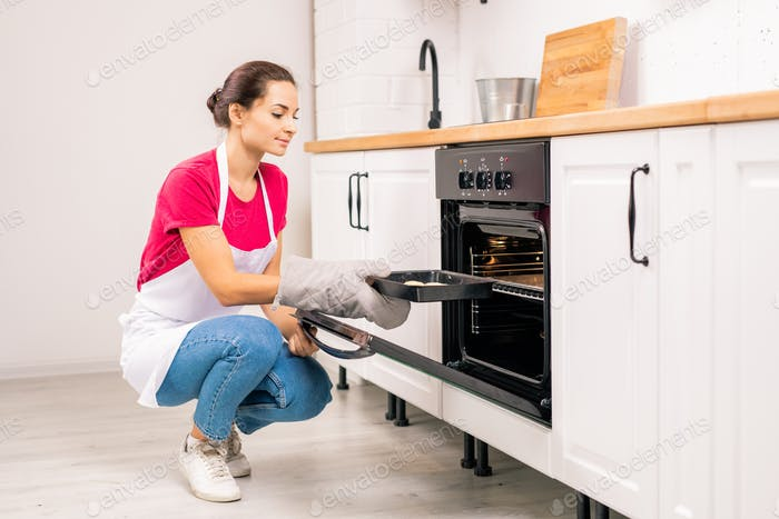 Young housewife squatting while putting tray with raw cookies into electric oven