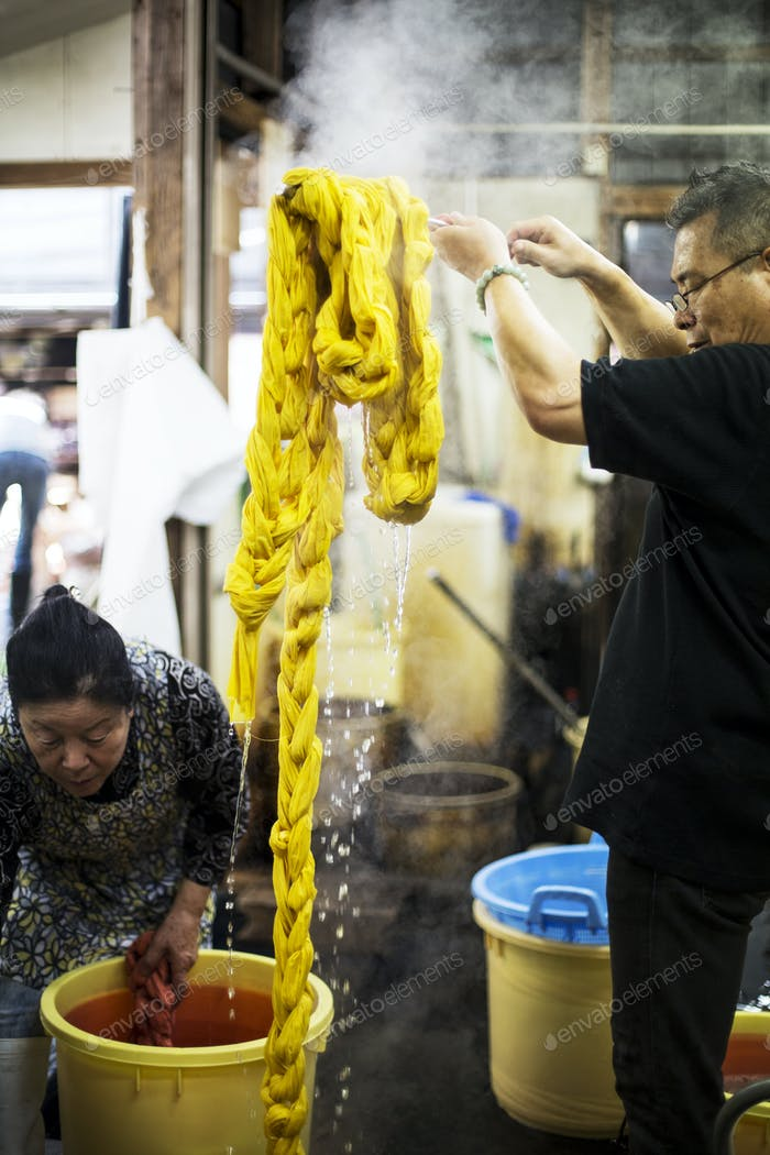 Japanese man standing in a textile plant dye workshop, holding aloft piece of freshly dyed bright