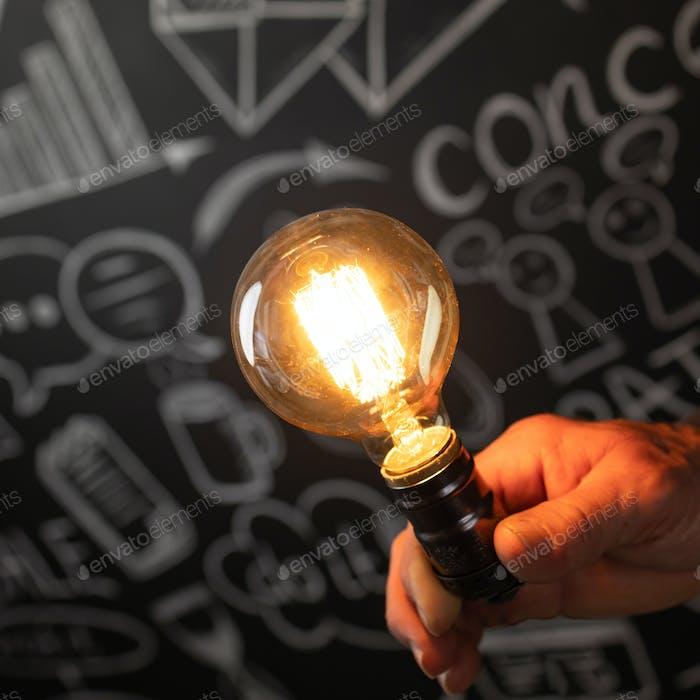 Businessman holding lightbulb in hand