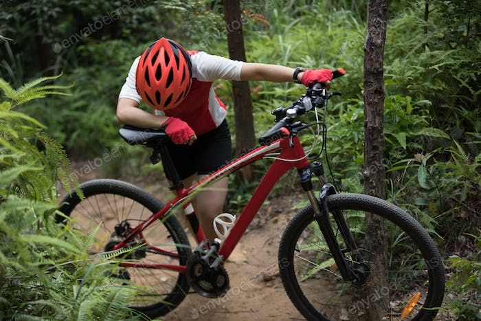 Tired female cyclist on mountain trail