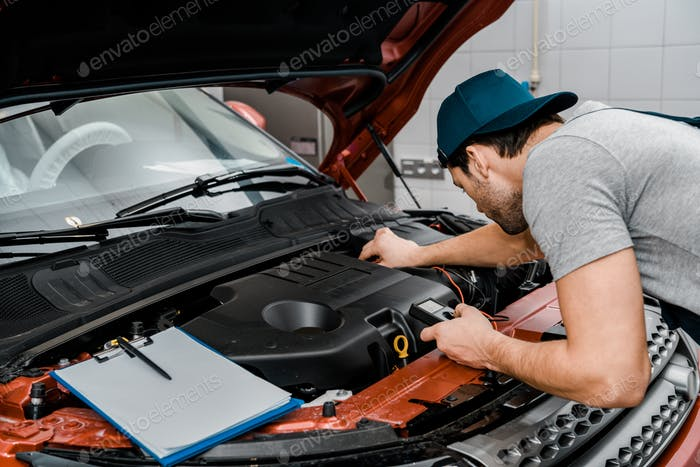auto mechanic with multimeter voltmeter checking car battery voltage at mechanic shop