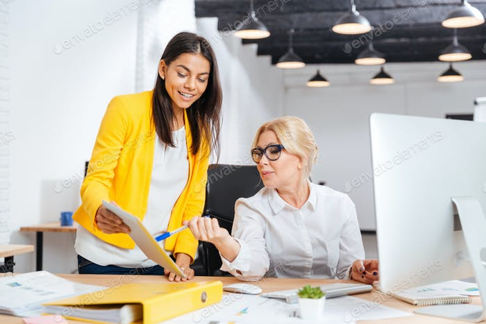 Two smiling businesswomen working together at the table in office