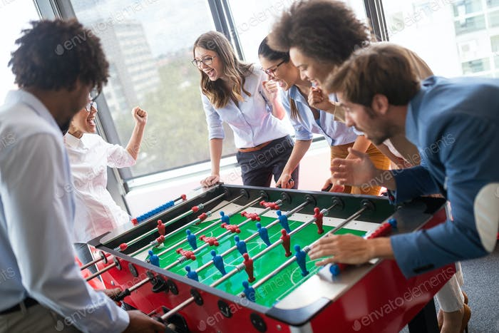 Colleagues playing table football in the break