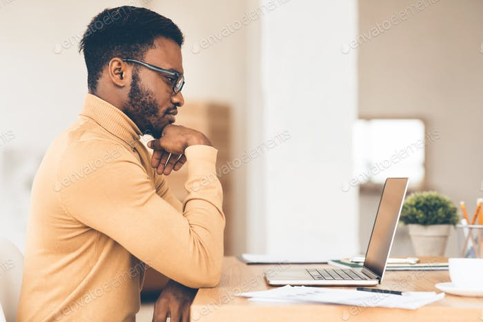 Black guy working on his laptop at home