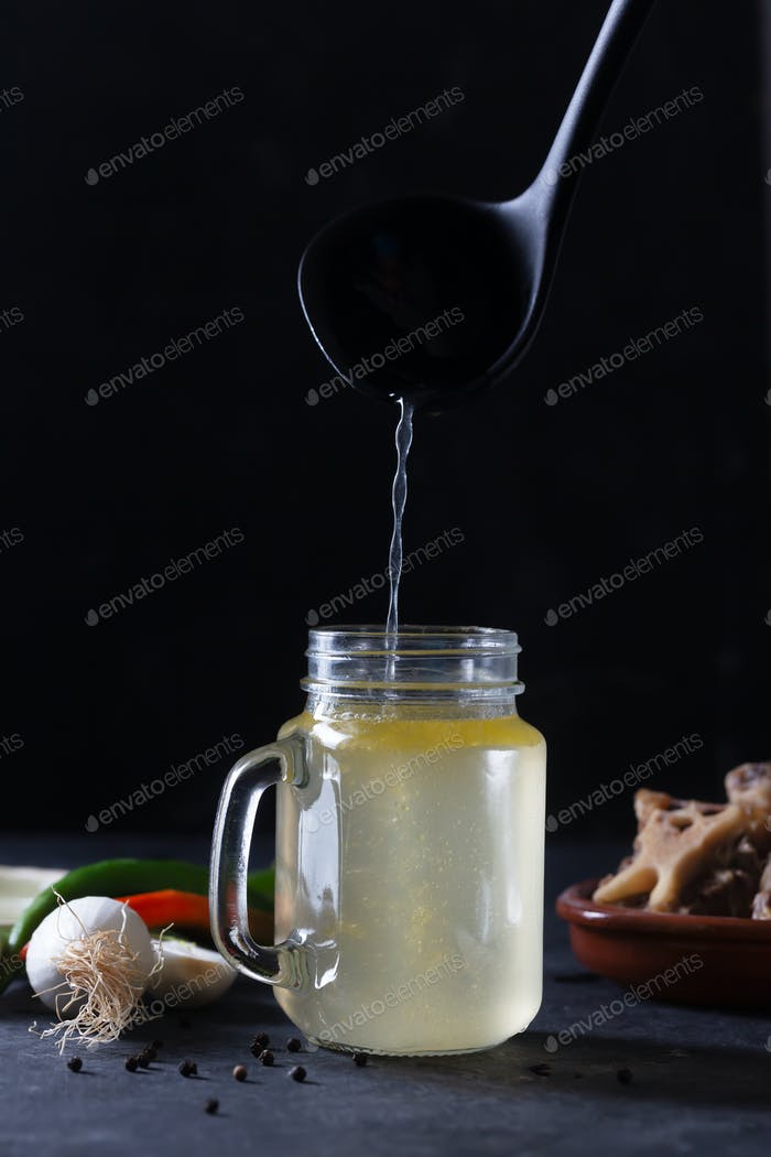 Pouring Homemade Beef Bone Broth in Glass Storage Jar on a black background
