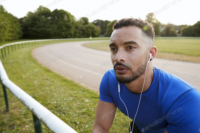 Male athlete wearing earphones at running track, close up