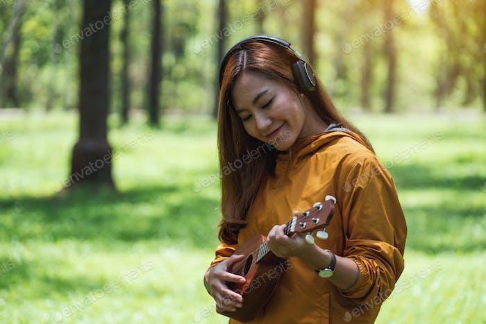 Eine schöne asiatische Frau hört gerne Musik mit Kopfhörern, während sie im Park Ukulele spielt
