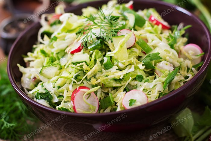 Vitamin salad of young vegetables: cabbage, radish, cucumber and fresh herbs