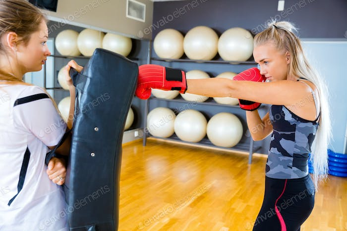 Two focused young women training boxing in fitness gym center