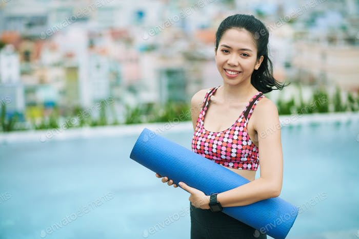 Asian girl with exercise mat