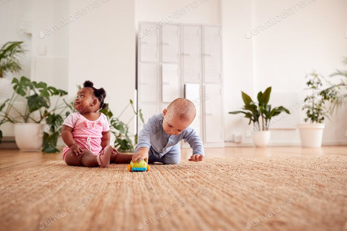 Baby Boy And Girl Playing With Toys On Rug At Home Together