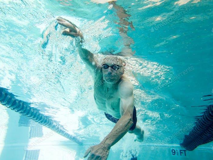 Athletischer Senior Mann in seiner Mitte 70er Jahren Schwimmen Runden, Blick von Unterwasser.