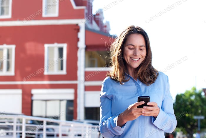 attractive older woman standing outside with mobile phone