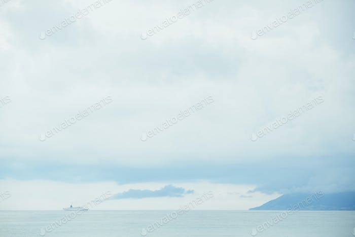 marine cruise ship on dramatic sky, sea and mountain landscape background
