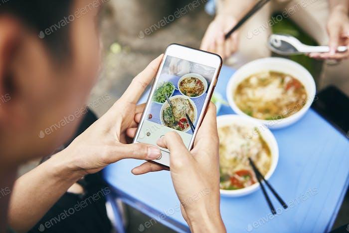 Nahaufnahme des Menschen fotografiert sein vietnamesisches Essen