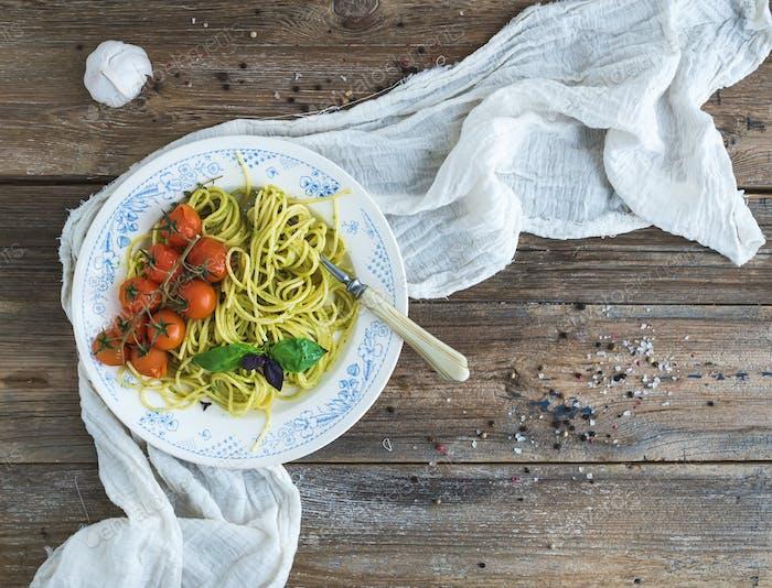 Pasta spaghetti with pesto sauce, basil, garlic, baked cherry-tomatoes
