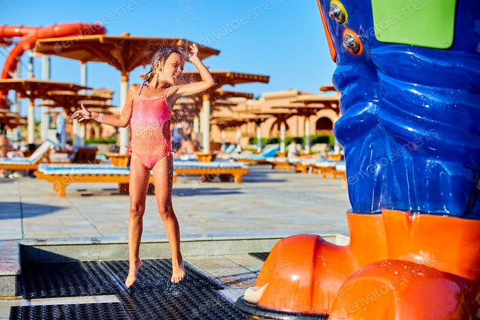 Funny little girl in swimsuit cooling in shower outside
