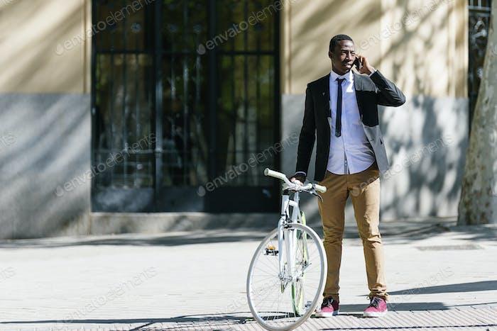 Африканский мужчина с мобильным телефоном и велосипедом.