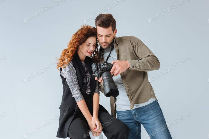 professional photographer and attractive model on fashion shoot in photo studio