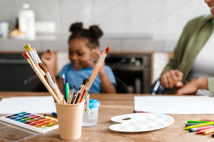 Happy mother drawing with her daughter at table in home kitchen