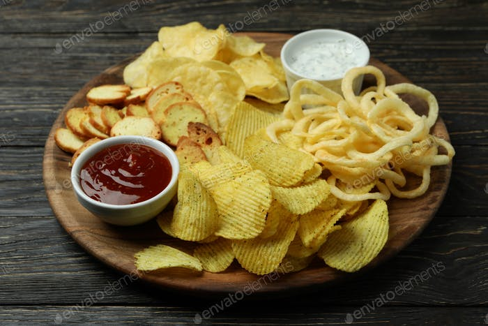 Tray with different snacks on wooden background