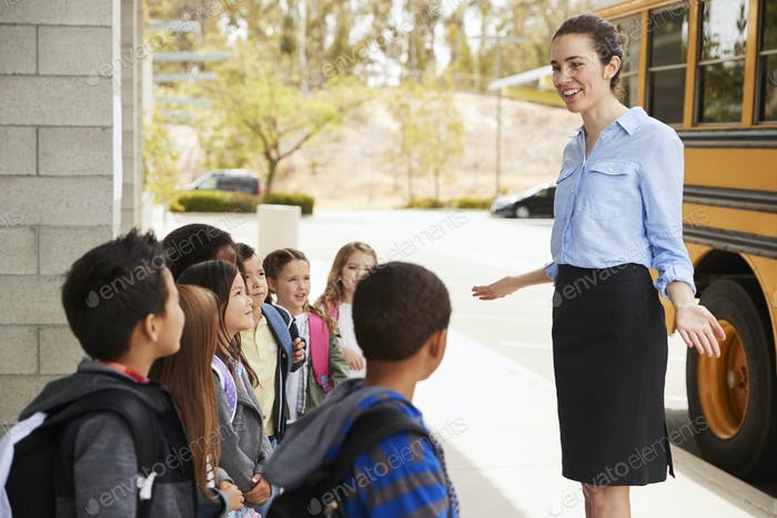 School teacher talking to kids before they get on school bus