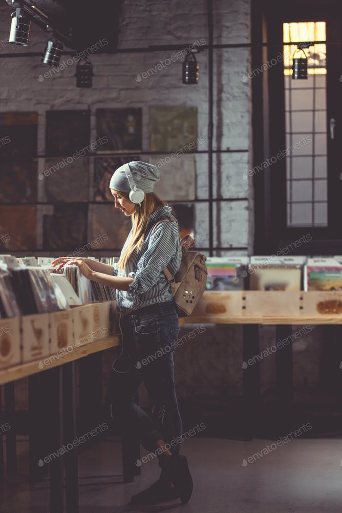 Young girl listening to music in a vinyl record store