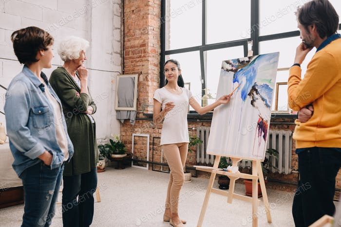 Young Woman Presenting Painting in Art Studio