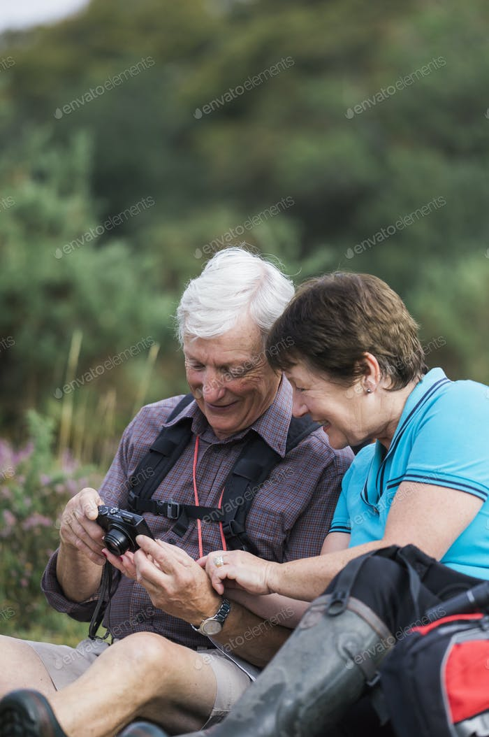 A mature couple taking photographs while out walking.