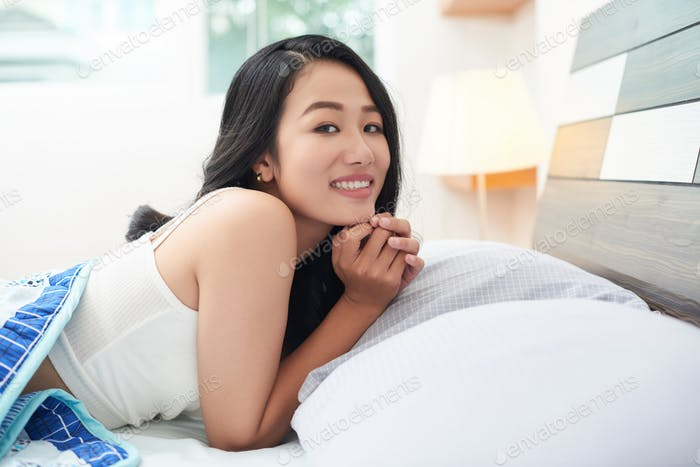 Beautiful Asian woman under blanket in bed