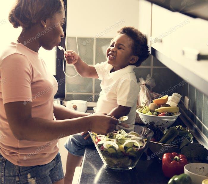 Schwarzes Kind Fütterung Mutter mit Kochen Essen in der Küche