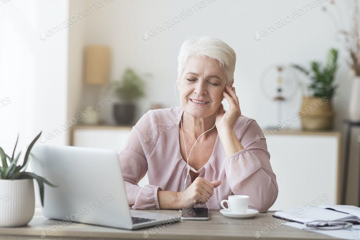 Aged business woman with earphones enjoying music