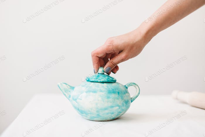 Close up photo of handmade blue teapot at pottery studio isolated