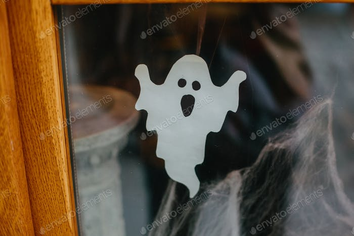Paper cut ghost and cobweb on door or window at store