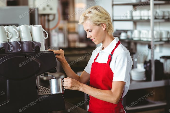 Pretty barista using the coffee machine at the cafe